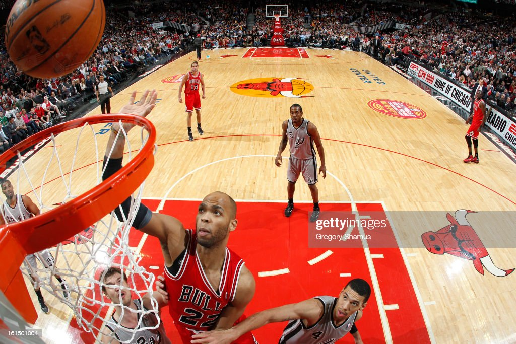Taj Gibson #22 of the Chicago Bulls drives to the basket against Tiago Splitter #22 and Danny Green #4 of the San Antonio Spurs on February 11, 2013 at the United Center in Chicago, Illinois.