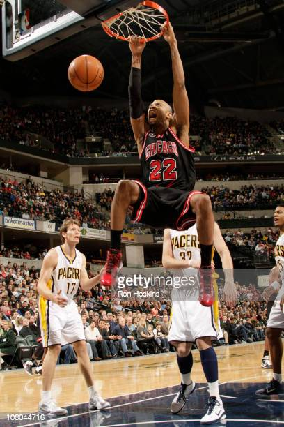 Taj Gibson of the Chicago Bulls dunks against Mike Dunleavy and Josh McRoberts of the Indiana Pacers on January 14 2011 at Conseco Fieldhouse in...