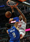 Taj Gibson of the Chicago Bulls dunks over Nikola Vucevic of the Orlando Magic at the United Center on December 16 2013 in Chicago Illinois The Magic...