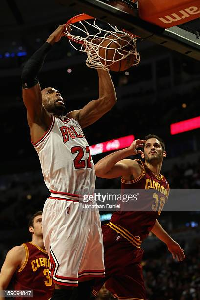 Taj Gibson of the Chicago Bulls dunks over Omir Casspi of the Cleveland Cavaliers at the United Center on January 7 2013 in Chicago Illinois The...
