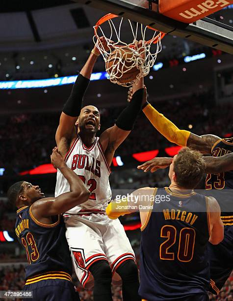 Taj Gibson of the Chicago Bulls dunks over Tristan Thompson and Timofey Mozgov of the Cleveland Cavaliers in Game Four of the Eastern Conference...