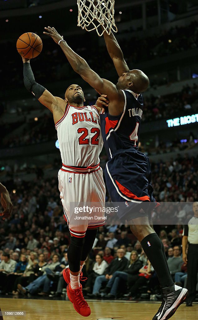 Taj Gibson #22 of the Chicago Bulls goes up for a dunk against Anthony Tolliver #4 of the Atlanta Hawks at the United Center on January 14, 2013 in Chicago, Illinois. The Bulls defeated the Hawks 97-58.