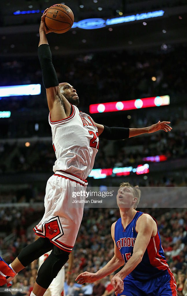 Taj Gibson of the Chicago Bulls goes up for a dunk over Kyle Singler of the Detroit Pistons at the United Center on April 11 2014 in Chicago Illinois...