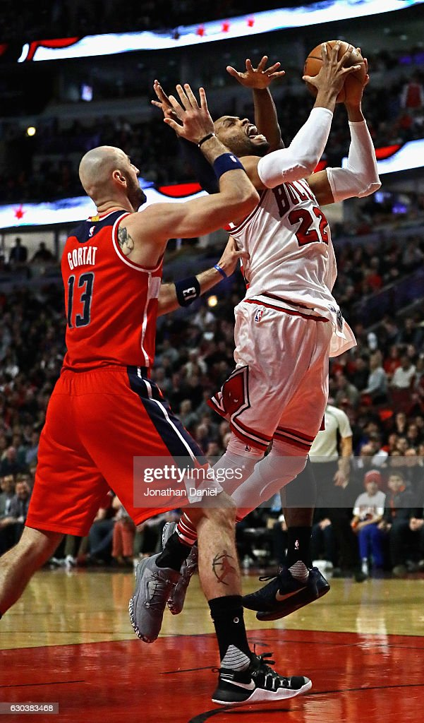 Taj Gibson #22 of the Chicago Bulls goes up for a shot between Marcin Gortat #13 and John Wall #2 of the Washington Wizards at the United Center on December 21, 2016 in Chicago, Illinois. The Wizards defeated the Bulls 107-97.