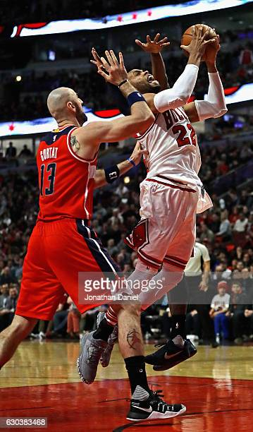 Taj Gibson of the Chicago Bulls goes up for a shot between Marcin Gortat and John Wall of the Washington Wizards at the United Center on December 21...