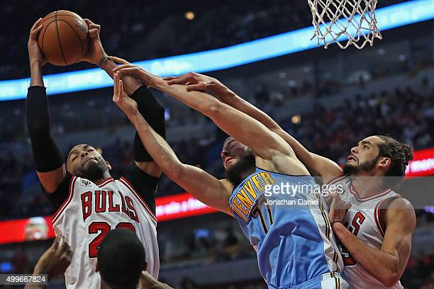 Taj Gibson of the Chicago Bulls grabs a rebound away from Joffrey Lauvergne of the Denver Nuggets as Joakim Noah applies defensive pressure at the...