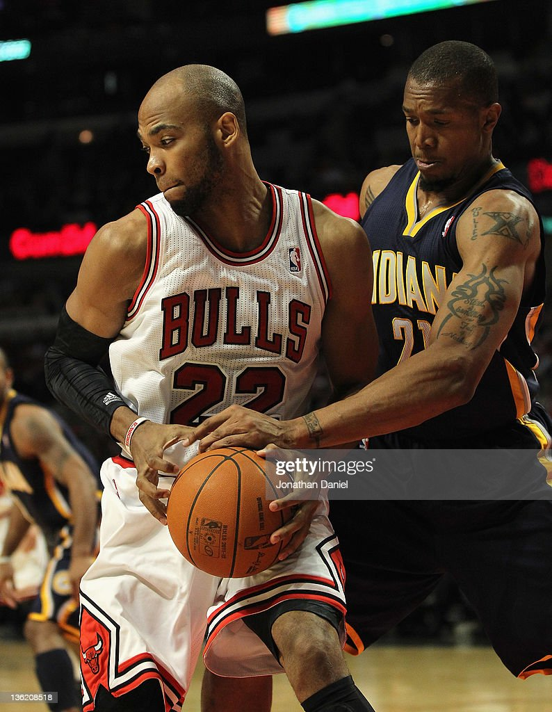 Taj Gibson #22 of the Chicago Bulls hangs onto the ball as it is slapped by David West #21 of the Indiana Pacers at the United Center on December 20, 2011 in Chicago, Illinois. The Bulls defeated the Pacers 93-85.