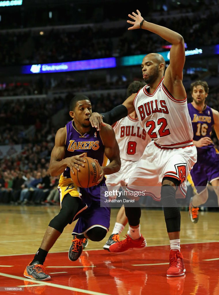 Taj Gibson #22 of the Chicago Bulls hits Darius Morris #1 of the Los Angeles Lakers in the mouth at the United Center on January 21, 2013 in Chicago, Illinois.