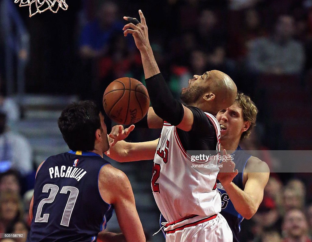 Taj Gibson #22 of the Chicago Bulls is fouled by Dirk Nowitzki #41 of the Dallas Mavericks as he tries to get off a shot against Zaza Pachulia #27 at the United Center on January 15, 2016 in Chicago, Illinois.