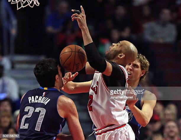 Taj Gibson of the Chicago Bulls is fouled by Dirk Nowitzki of the Dallas Mavericks as he tries to get off a shot against Zaza Pachulia at the United...