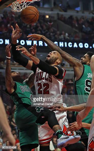 Taj Gibson of the Chicago Bulls is fouled while shooting between Isaiah Thomas and Amir Johnson of the Boston Celtics at the United Center on January...