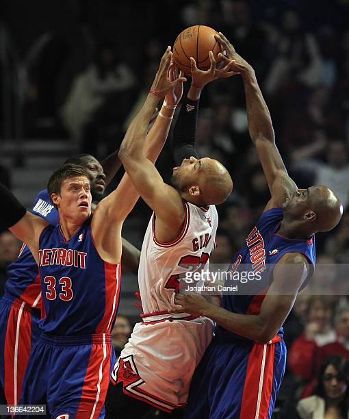Taj Gibson of the Chicago Bulls is pressured while shooting by Jonas Jerebko and Damien Wilkins of the Detroit Pistons at the United Center on...