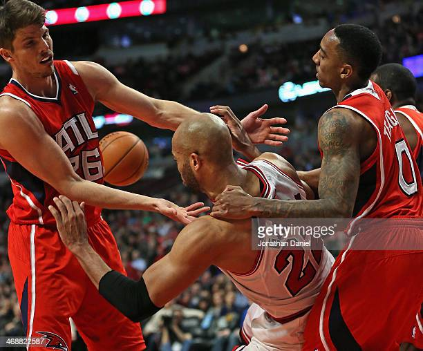 Taj Gibson of the Chicago Bulls is pulled to the ground by Jeff Teague of the Atlanta Hawks for a flagrant foul as Kyle Korver tries for the ball at...