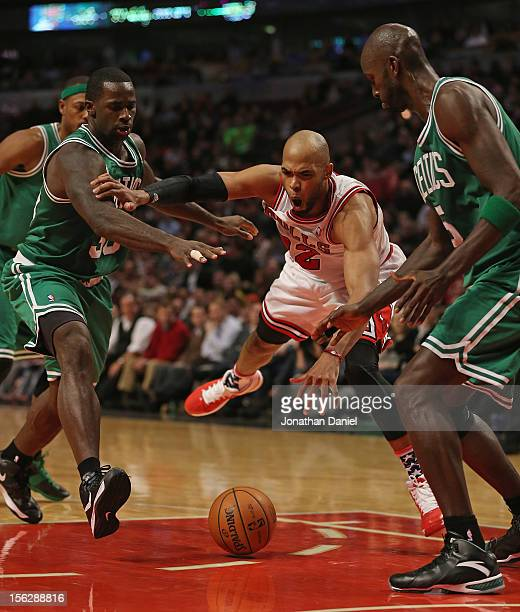 Taj Gibson of the Chicago Bulls looses control of the ball between Brandon Bass and Kevin Garnett of the Boston Celtics at the United Center on...
