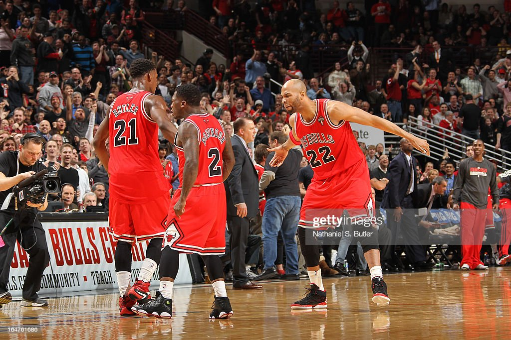 Taj Gibson #22 of the Chicago Bulls motivates teammates Jimmy Butler #21 and Nate Robinson #2 during the game against the Miami Heat on March 27, 2013 at the United Center in Chicago, Illinois.