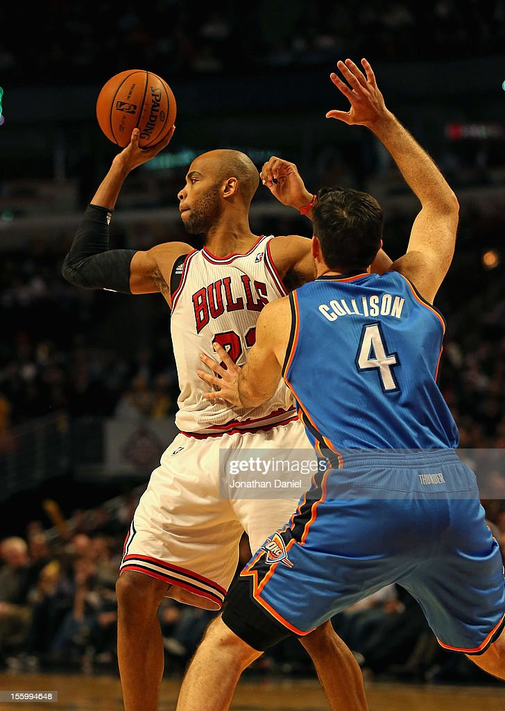 Taj Gibson #22 of the Chicago Bulls passes under pressure from Nick Collison #4 of the Oklahoma City Thunder at the United Center on November 8, 2012 in Chicago, Illinois.The Thunder defeated the Bulls 97-91.