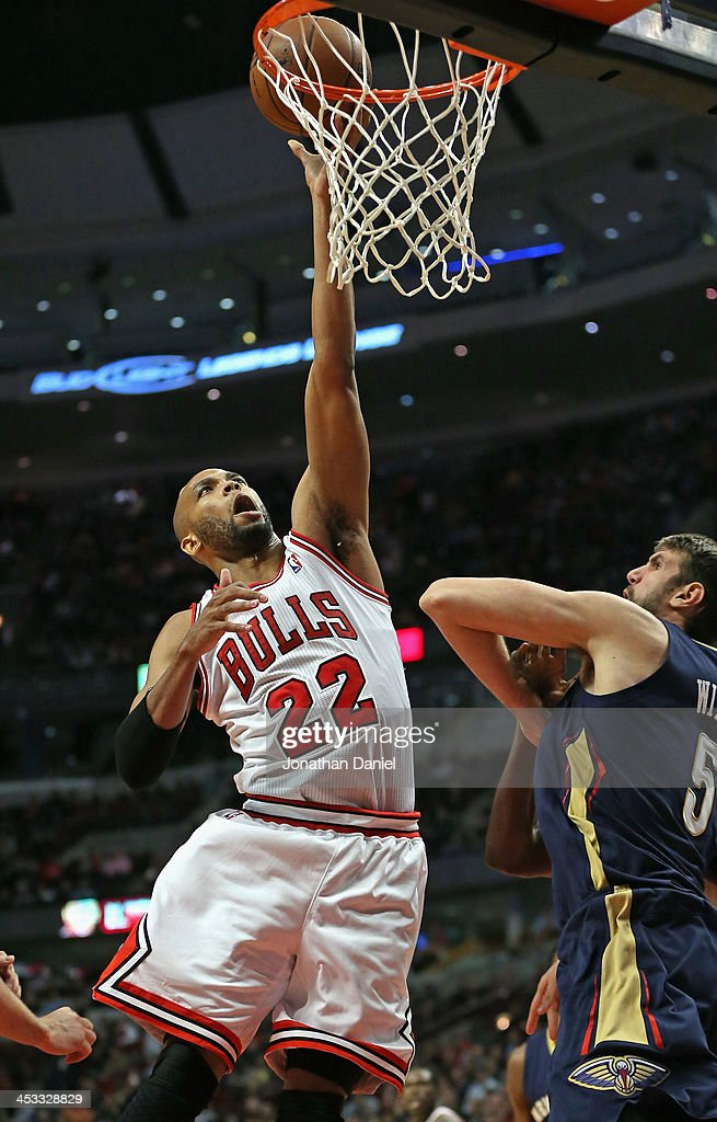 Taj Gibson #22 of the Chicago Bulls puts up a shot over Jeff Withey #5 of the New Orleans Pelicans at the United Center on December 2, 2013 in Chicago, Illinois. The Pelicans defeated the Bulls 131-128 in triple overtime.