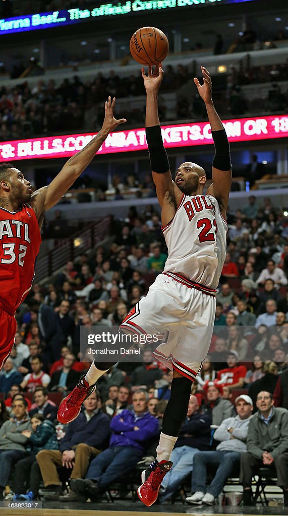 Taj Gibson #22 of the Chicago Bulls puts up a shot over Mike Scott #32 of the Atlanta Hawks on his way to a game-high 24 points at the United Center on February 11, 2014 in Chicago, Illinois. The Bulls defeated the Hawks 100-85.