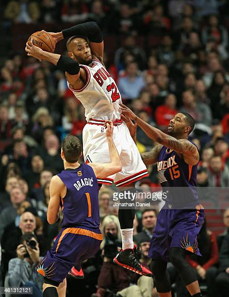 Taj Gibson of the Chicago Bulls rebounds over Goran Dragic and Marcus Morris of the Phoenix Suns at the United Center on January 7 2014 in Chicago...