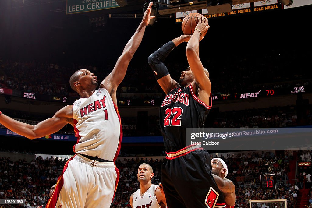 Taj Gibson #22 of the Chicago Bulls shoots against Chris Bosh #1 of the Miami Heat on January 4, 2013 at American Airlines Arena in Miami, Florida.