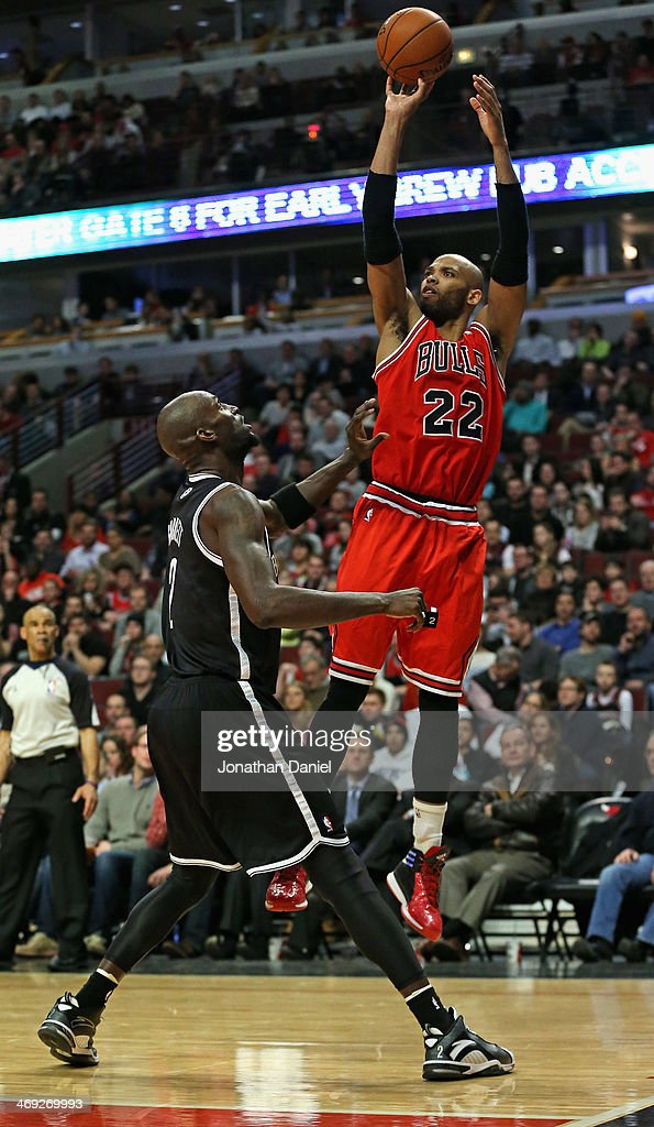 Taj Gibson #22 of the Chicago Bulls shoots over Kevin Garnett #2 of the Brooklyn Nets on his way to game-high 16 points at the United Center on February 13, 2014 in Chicago, Illinois. The Bulls defeated the Nets 92-76.