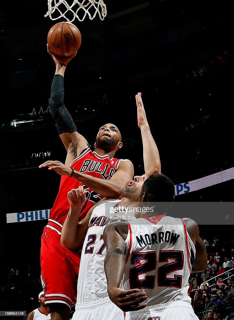 Taj Gibson #22 of the Chicago Bulls shoots over Zaza Pachulia #27 and Anthony Morrow #22 of the Atlanta Hawks at Philips Arena on December 22, 2012 in Atlanta, Georgia.