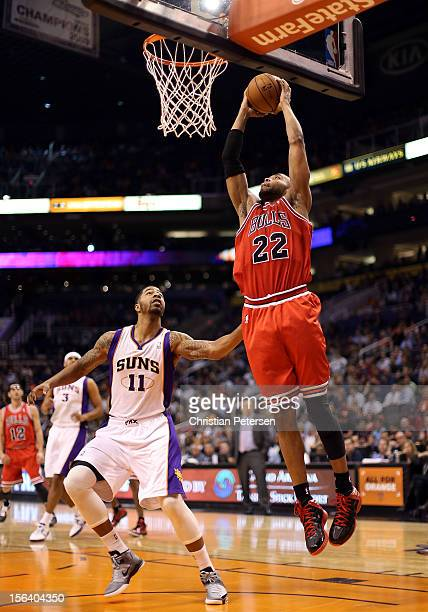 Taj Gibson of the Chicago Bulls slam dunks the ball over Markieff Morris of the Phoenix Suns during the NBA game at US Airways Center on November 14...