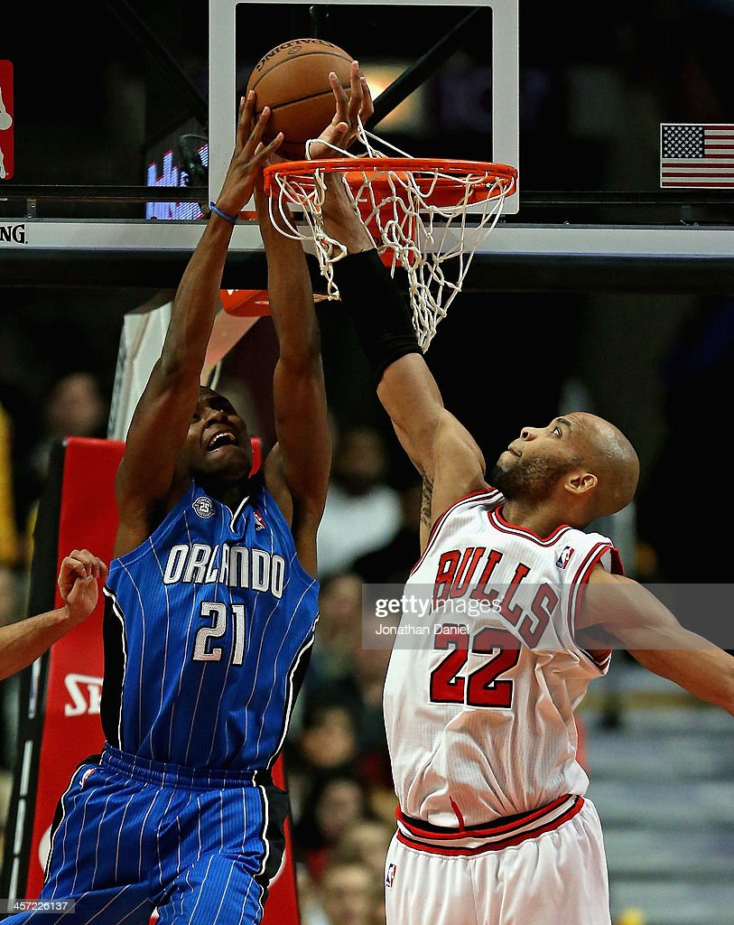 Taj Gibson #22 of the Chicago Bulls sticks his hand through the basket to knock away a shot by Maurice Harkless #21 of the Orlando Magic at the United Center on December 16, 2013 in Chicago, Illinois. The Magic defeated the Bulls 83-82.