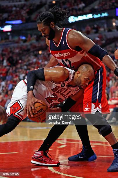 Taj Gibson of the Chicago Bulls tries to move against Nene of the Washington Wizards in Game One of the Eastern Conference Quarterfinals during the...