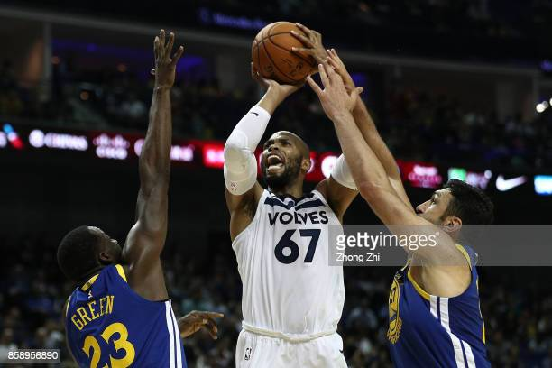 Taj Gibson of the Minnesota Timberwolves in action against Draymond Green and Zaza Pachulia of the Golden State Warriors during the game between the...