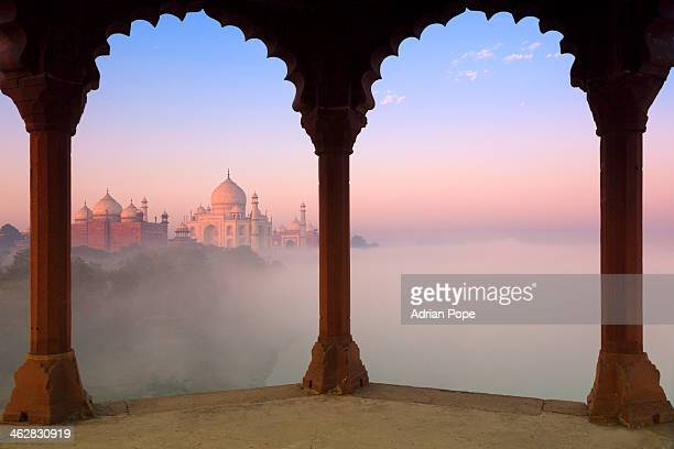 Taj Mahal in fog framed by arches