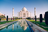 The magnificent Taj Mahal in Agra, India in all its beauty. People are visible on each sidewalk.