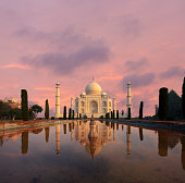 Nobody present as Taj Mahal glows beautifully at sunset reflected in front garden water fountain pool of water under a dramatic pink sky in Agra, Uttar Pradesh, India. Plenty of copy space