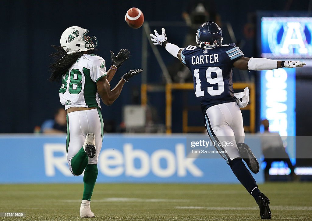 Taj Smith #88 of the Saskatchewan Roughriders catches a pass for a touchdown during CFL game action as Jalil Carter #19 of the Toronto Argonauts defends on July 11, 2013 at Rogers Centre in Toronto, Ontario, Canada.