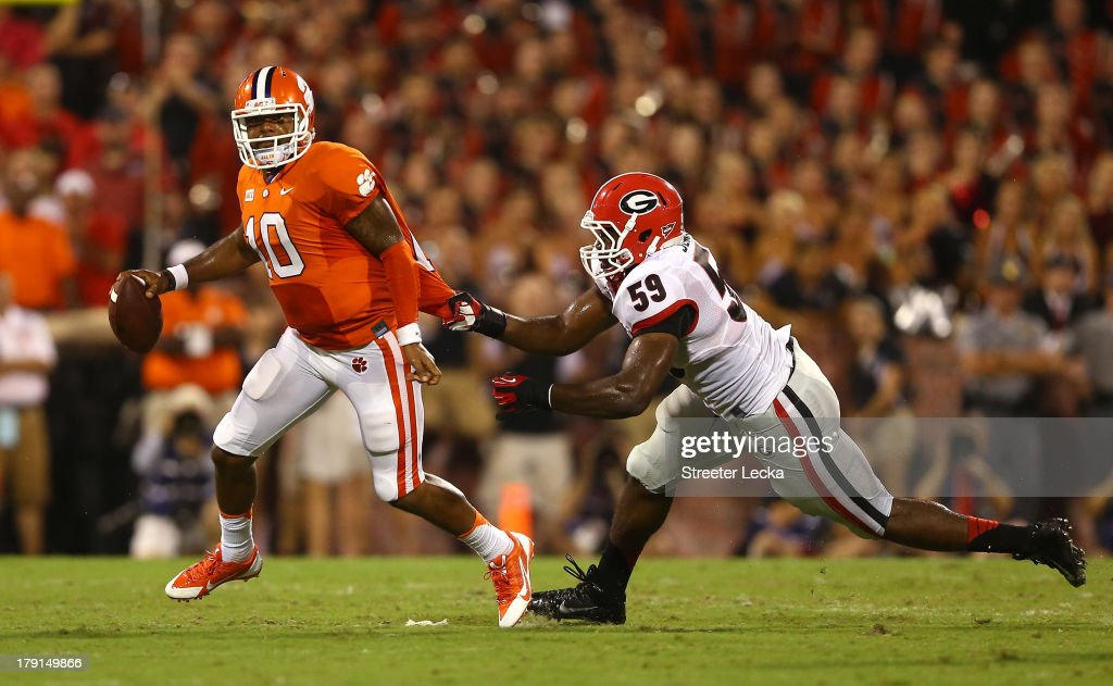 <a gi-track='captionPersonalityLinkClicked' href=/galleries/search?phrase=Tajh+Boyd&family=editorial&specificpeople=7352415 ng-click='$event.stopPropagation()'>Tajh Boyd</a> #10 of the Clemson Tigers avoids being tackled by Jordan Jenkins #59 of the Georgia Bulldogs in the second quarter at Memorial Stadium on August 31, 2013 in Clemson, South Carolina.