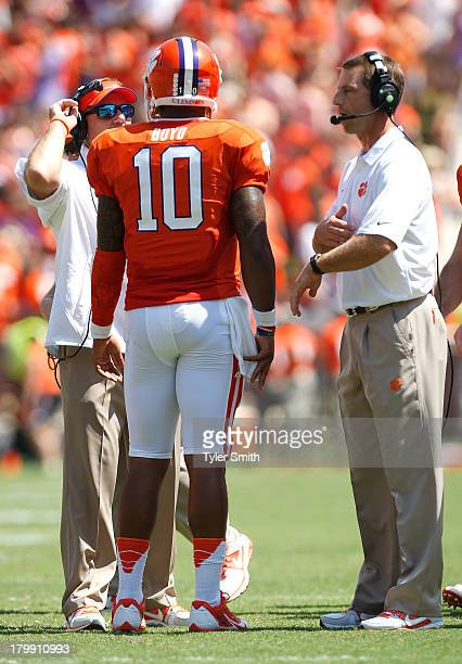 Tajh Boyd of the Clemson Tigers talks with Head Coach Dabo Swinney and Offensive Coordinator Chad Morris during a timeout during the game against the...