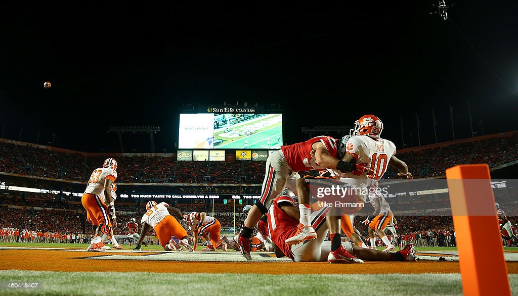 <a gi-track='captionPersonalityLinkClicked' href=/galleries/search?phrase=Tajh+Boyd&family=editorial&specificpeople=7352415 ng-click='$event.stopPropagation()'>Tajh Boyd</a> #10 of the Clemson Tigers throws the ball away and is called for intentional grounding resulting in a safety as Joey Bosa #97 and Joshua Perry #37 of the Ohio State Buckeyes defend in the first quarter during the Discover Orange Bowl at Sun Life Stadium on January 3, 2014 in Miami Gardens, Florida.