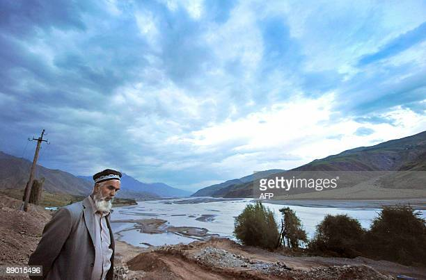 Tajik stand on the river bank in the village of Garm some 250km from Dushanbe on July 12 2009 A secretive military operation has raised fears that...
