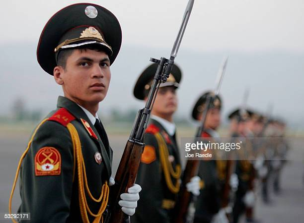 Tajikistan army soldiers stand to attention as US Secretary of Defense Donald Rumsfeld prepares to walk to his waiting US Air force plane on his way...