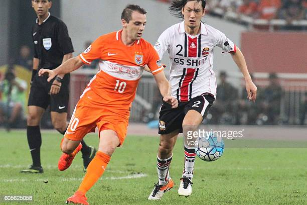 Takahagi Yojiro of FC Seoul competes the ball with Walter Montillo of Shandong Luneng during the quarter final match of AFC Asian Champions League...