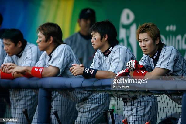 Takahiro Arai Hiroyuki Nakajima Norichika Aoki and Tsuyoshi Nishioka of Japan stand in the dugout after losing to Korea in the men's semifinal game...