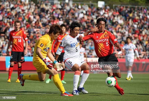 Takahiro Masukawa of Nagoya Grampus competes for the ball against Kazuhiko Chiba and Shusaku Nishikawa of Sanfrecce Hiroshima during the JLeague...