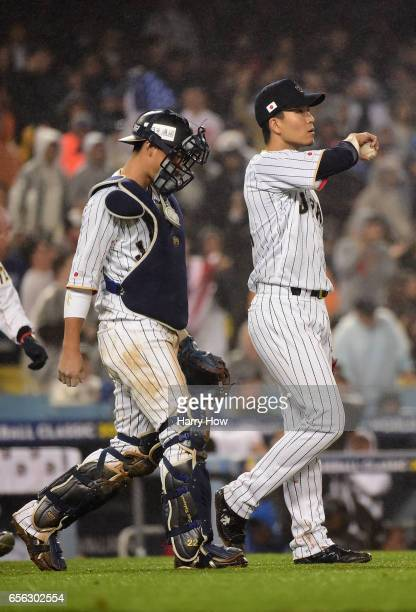 Takahiro Norimoto and Seiji Kobayashi of team Japan react in the eighth inning against team United States during Game 2 of the Championship Round of...
