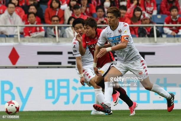 Takahiro Sekine of Urawa Red Diamonds and Hiroki Miyazawa of Consadole Sapporo compete for the ball during the JLeague J1 match between Urawa Red...