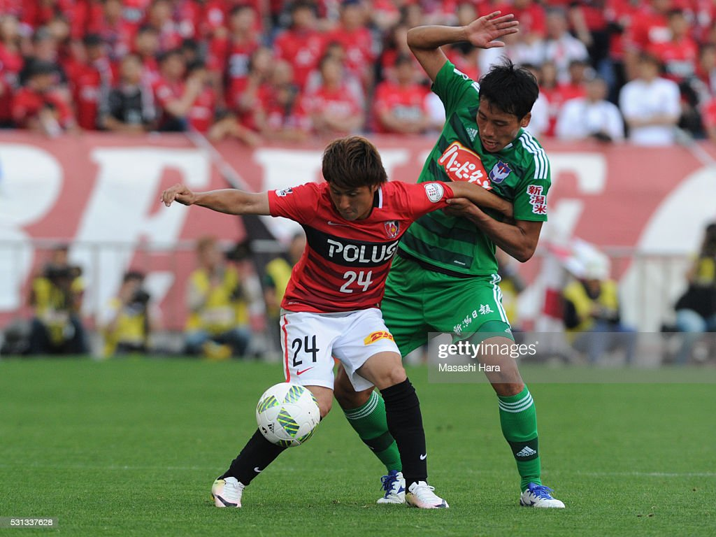 Takahiro Sekine #24 of Urawa Red Diamonds and Shu Hiramatsu #16 of Albirex Nigata compete for the ball during the J.League match between Urawa Red Diamonds and Albirex Nigata at the Saitama stadium on May 14, 2016 in Saitama, Japan.