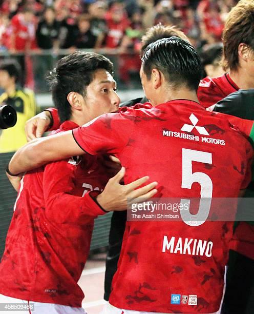 Takahiro Sekine of Urawa Red Diamonds celebrates scoring his team's first goal with his teammate Tomoaki Makino during the JLeague match between...