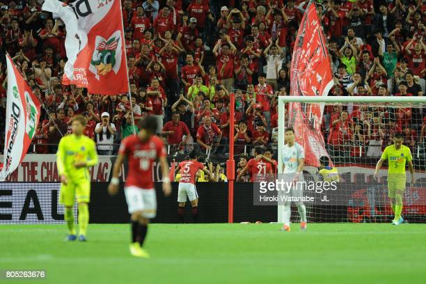 Takahiro Sekine of Urawa Red Diamonds celebrates scoring their team's fourth goal with his team mates during the JLeague J1 match between Urawa Red...