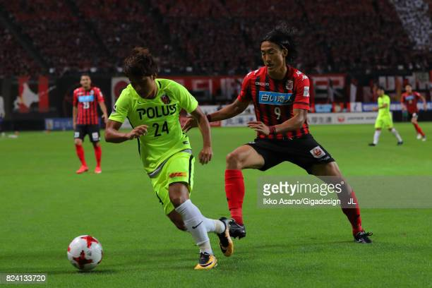 Takahiro Sekine of Urawa Red Diamonds controls the ball under pressure of Ken Tokura of Consadole Sapporo during the JLeague J1 match between...