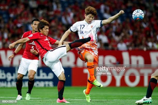 Takahiro Sekine of Urawa Reds Diamonds defends Ahn Hyunbeom of Jeju United during the AFC Champions League Round of 16 match between Urawa Red...