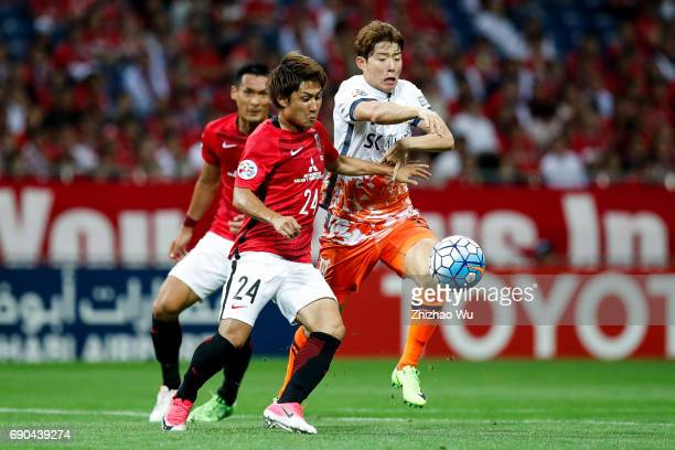 Takahiro Sekine of Urawa Reds Diamonds defends Lee Changmin of Jeju United during the AFC Champions League Round of 16 match between Urawa Red...